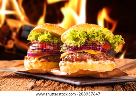hamburger with fries on wooden table and fire background - stock photo