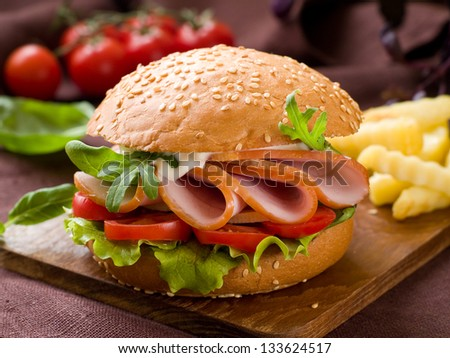 Hamburger with ham, tomato and lettuce, selective focus - stock photo