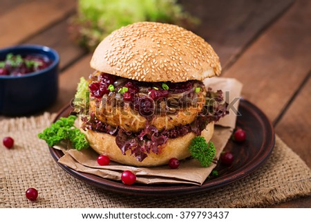 Hamburger with juicy turkey burger with cheese, caramelized onions and cranberry sauce - stock photo