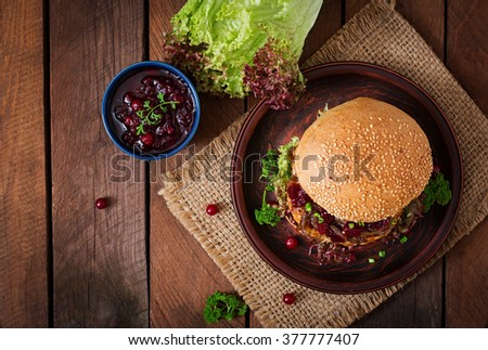 Hamburger with juicy turkey burger with cheese, caramelized onions and cranberry sauce. Top view - stock photo