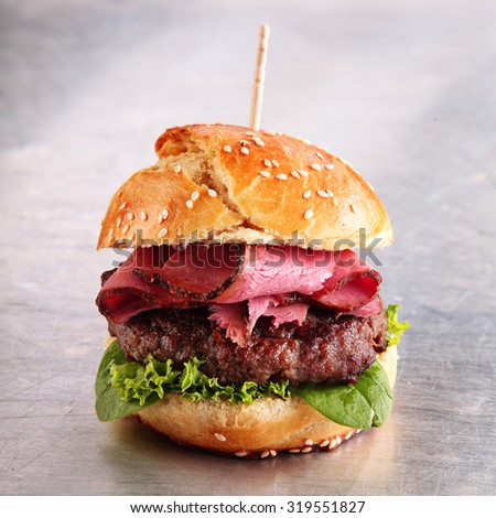 Hamburger with sliced roast beef on a juicy beef patty served with lettuce on a freshly baked sesame bun over a metallic silver background - stock photo