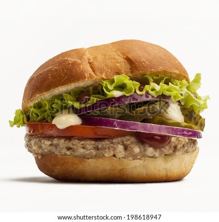 Hamburger with tomato, red onion, pickles and lettuce isolated on white background. - stock photo