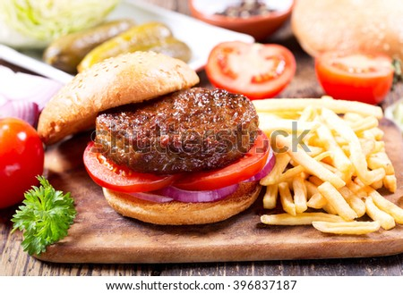 hamburger with vegetables and fries on a wooden table - stock photo