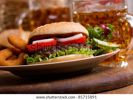 hamburger with vegetables and mug of beer - stock photo