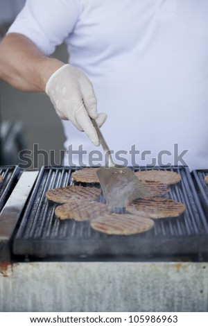 Hamburgers being cooked on the hot grill - stock photo