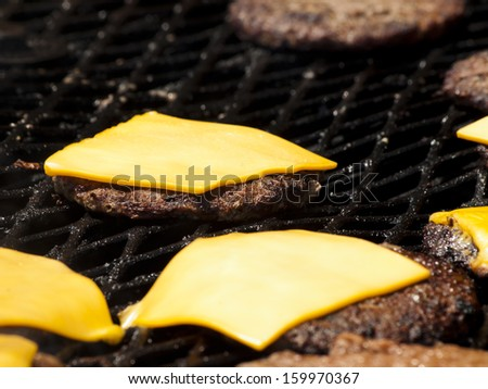 Hamburgers being flame broiled on the gas grill. Shallow depth of field. - stock photo
