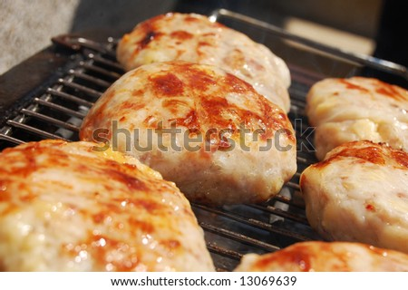 Hamburgers cooking on barbeque grill (shallow DOF) - stock photo