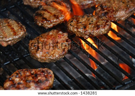 Hamburgers cooking on barbeque grill with flames - stock photo