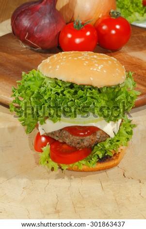 Hamburgers, fast food, burger, hamburger steak with salad, tomato, cheese, cucumber on a wooden chopping board - stock photo