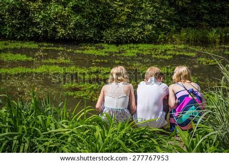HAMILTON TOWNSHIP NEW JERSEY - MAY 9: Three children look into a pond at the Azalea Festival on May 9 2015 in Hamilton Township New Jersey. - stock photo