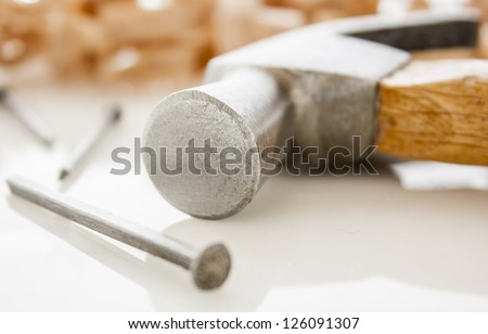 hammer and nails on a wood board with sawdust shavings - stock photo