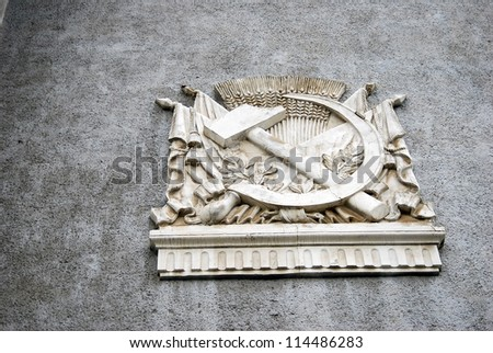 Hammer and sickle, symbol of Soviet Union (USSR) on grey background. Architecture of All-Russia Exhibition Center - VVC (former name - Exhibition of Economic Achievements - VDNH) in Moscow, Russia. - stock photo