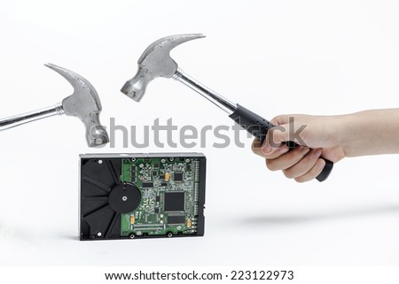 Hammer destroying hard disk on a white background - stock photo