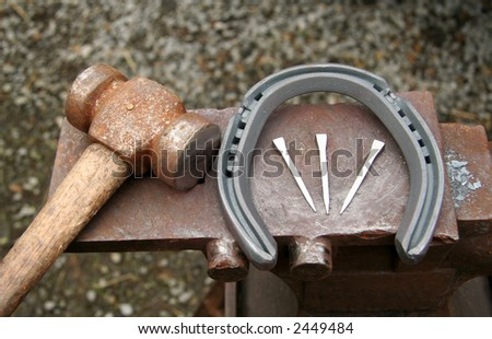 Hammer, horseshoe and nails rest on the blacksmiths anvil - stock photo