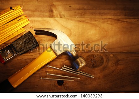 Hammer, nails, ruler and brush on wood - stock photo