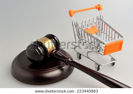 Hammer of judge and pushcart on gray background - stock photo