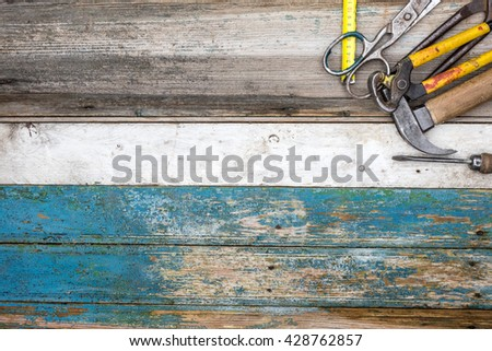 Hammer, screwdriver, wrench, chisel, tape measure and other  workshop tools. Vintage set of hand tools on a old wooden background  with space for copy - stock photo