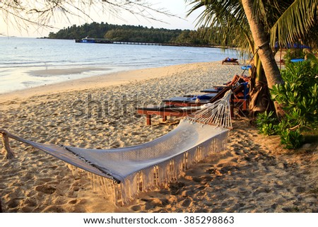 Hammock at the beach on a tropical paradise island. The hammock is empty and hangs low over a white sand beach. See is visible on the background.  - stock photo