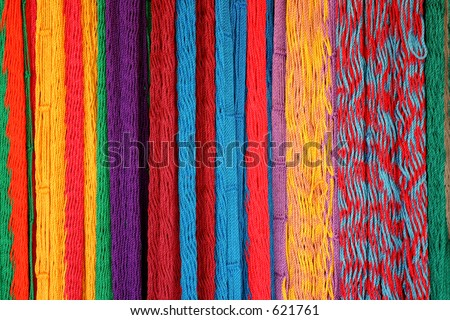 Hammocks hung on the wall in bright colors inviting tourist to buy them. - stock photo