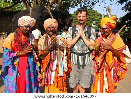 HAMPI, KARNATAKA, INDIA - APRIL 2013: Local men in traditional clothes with tourist - stock photo