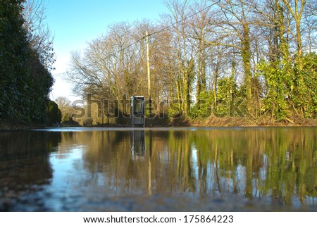 HAMPRESTON, DORSET, UK, FEBRUARY 9, 2014. Flooded road with telephone booth after severe and prolonged storms along the South coast of England. Low down view. - stock photo