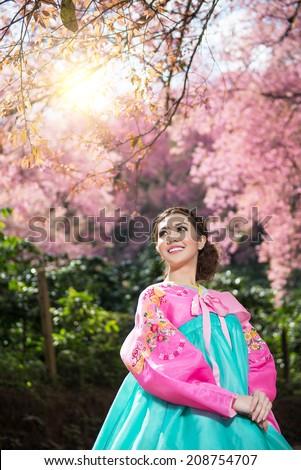 Hanbok: the traditional Korean dress and beautiful Asian girl with sakura - stock photo