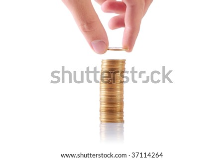 hand adding a coin to a stack of coins - stock photo