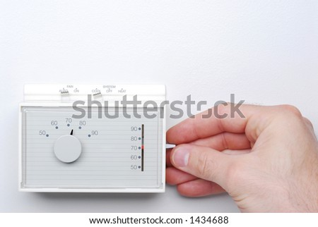 Hand Adjusting Thermostat - stock photo