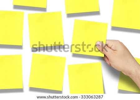Hand affixing or taking blank square yellow postit note on whiteboard full of postits - stock photo