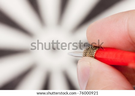 Hand aiming to target by red dart - stock photo