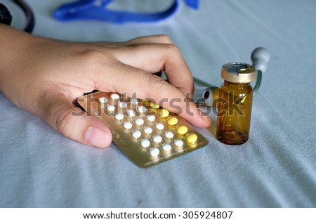 Hand and  birth control pill - stock photo