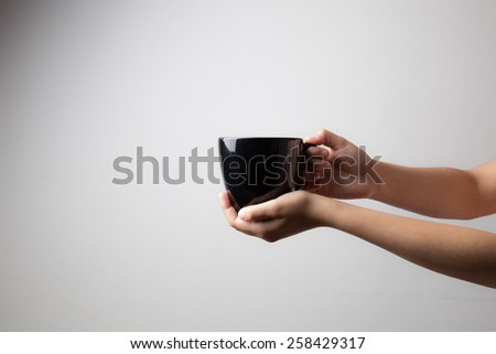 hand and black coffee mug - stock photo