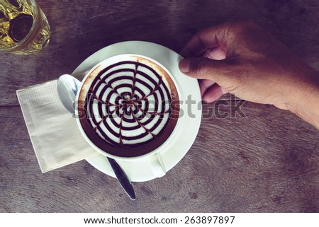 hand and coffee cup with vintage blend - stock photo