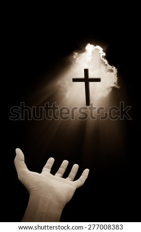 Hand and cross on light beam background - stock photo
