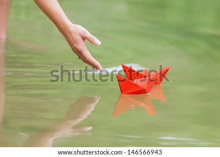 hand and paper boat in river - stock photo
