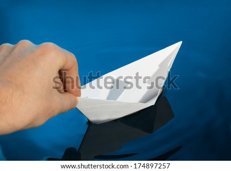 Hand and paper boat. Launching a ship. - stock photo