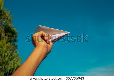 Hand and paper plane in the sky - stock photo