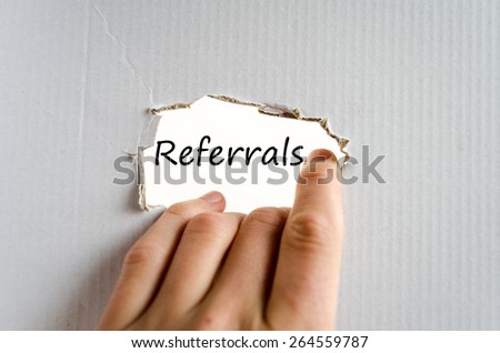 Hand and text Referrals on the cardboard background - business concept - stock photo