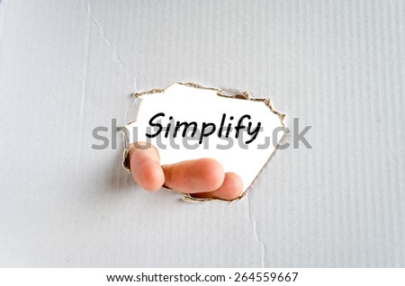 Hand and text Simplify on the cardboard background - business concept - stock photo