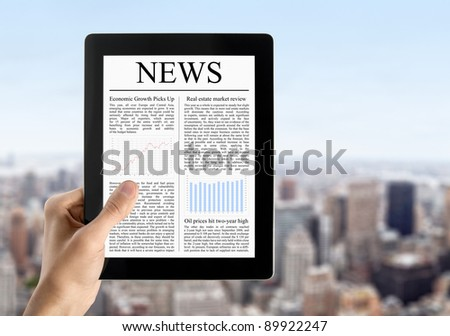 Hand are holding digital tablet pc  with fresh news. Blurred cityscape with skyscrapers on background. - stock photo