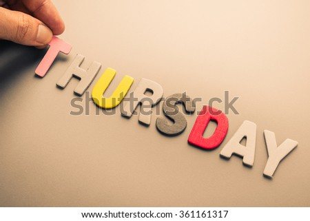 Hand arrange wood letters as Thursday word - stock photo