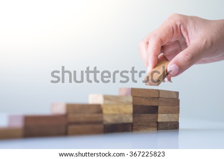 Hand arranging wood block stacking as step stair. Business concept for growth success process. - stock photo