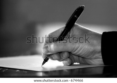 Hand at desk signing paperwork/document/contract or making notes - Black and White image. - stock photo