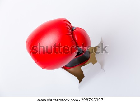 Hand break through paper with boxing gloves - stock photo