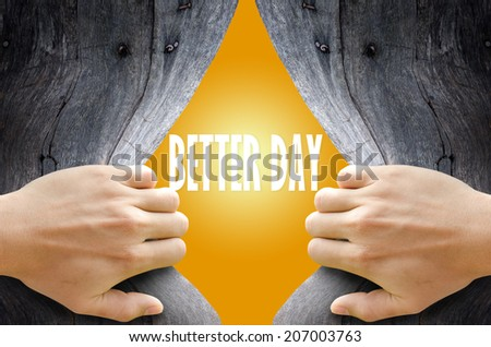 """Hand breaking a wooden wall found the word """"BETTER DAY"""" on the bright yellow background. - stock photo"""