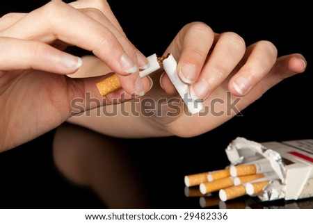 Hand breaking the last cigarette to stop smoking - stock photo