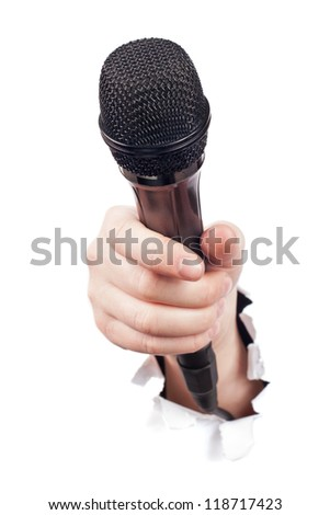 Hand breaking white paper surface holding microphone - stock photo