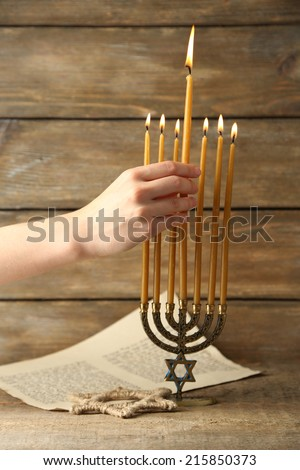 Hand burning candles on Menorah on wooden background - stock photo