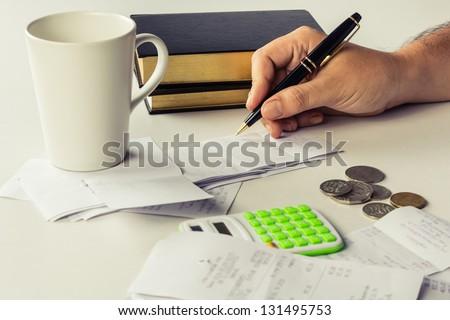 Hand calculating bills on the desk - stock photo