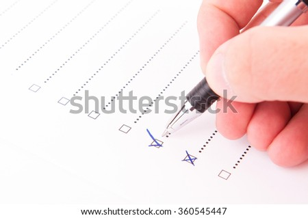 Hand checking a box with a yes with a pen - stock photo
